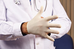 Doctor putting glove on. Doctor putting medical glove on for protection Stock Photo