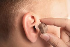Doctor putting hearing aid in patient`s ear royalty free stock photos