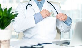 Doctor putting hundred dollar bill into his pocket. Accepting bribe Royalty Free Stock Photo