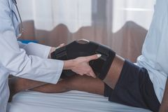 Doctor putting on knee brace. Cropped image of doctor putting on knee brace to african american patient stock photos