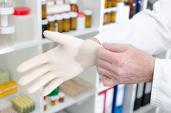 Doctor putting on a latex glove Stock Photo