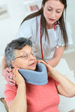 Doctor putting neck brace on woman Stock Photography
