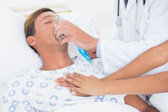 Doctor putting an oxygen mask Stock Images