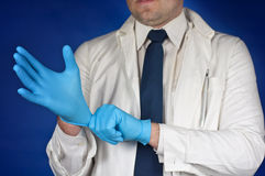 Doctor putting on protective gloves  on blue Royalty Free Stock Photography