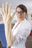 Doctor putting on surgical glove with attitude in examination room Stock Photography