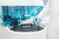 Doctor putting tubes of blood in centrifugal machine for testing. And analyzing stock photography