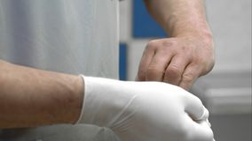 Doctor putting on white sterilized surgical glove. Close up. Professional shot in 4K resolution. 094. You can use it e.g. in your commercial video, business Royalty Free Stock Photography