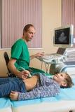 Doctor que analiza al paciente del muchacho con el abdomen Foto de archivo