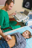 Doctor que analiza al paciente del muchacho con el abdomen Fotos de archivo