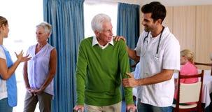 Doctor que ayuda a seniorman para caminar con el caminante almacen de metraje de vídeo