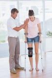Doctor que ayuda a su paciente que camina con la muleta imagenes de archivo