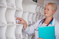 Doctor que busca la carta médica en clínica Fotografía de archivo