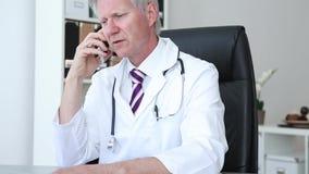 Doctor que charla en su teléfono móvil almacen de metraje de vídeo