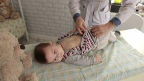 La Enfermera Desnuda Al Bebé En El Chequeo De La Clínica Metrajes