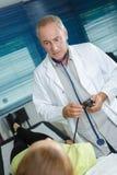 Doctor que comprueba al paciente imagen de archivo libre de regalías