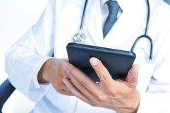 Doctor que comprueba hacia fuera el suyo tableta Fotos de archivo