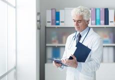 Doctor que comprueba informes médicos imagen de archivo libre de regalías