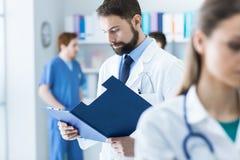 Doctor que comprueba informes médicos imagenes de archivo