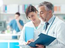 Doctor que comprueba informes médicos con su ayudante fotos de archivo libres de regalías