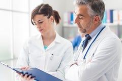 Doctor que comprueba informes médicos con su ayudante imagen de archivo