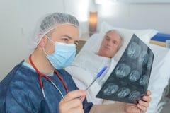 Doctor que comprueba la película del rayo de x con el paciente fotografía de archivo libre de regalías