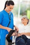 Doctor que comprueba la presión arterial Foto de archivo libre de regalías