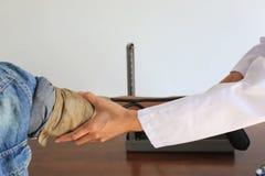 Doctor que comprueba la presión arterial de un paciente en el hospital, Medicin foto de archivo