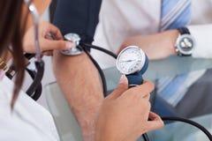Doctor que comprueba la presión arterial del hombre de negocios Imágenes de archivo libres de regalías