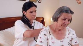 Doctor que comprueba los pulmones mayores de la mujer con el estetoscopio en casa metrajes