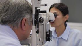 Doctor que comprueba ojos mayores de los pacientes almacen de metraje de vídeo