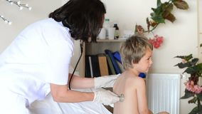 Doctor que consulta a un niño almacen de metraje de vídeo