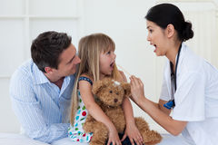 Doctor que controla la garganta de la niña Imagen de archivo