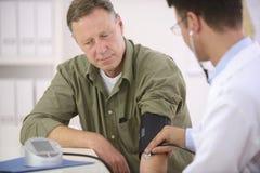 Doctor que controla la presión arterial Imagen de archivo libre de regalías