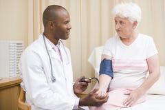 Doctor que controla la presión arterial de la mujer Foto de archivo
