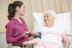 Doctor que controla la presión arterial de la mujer Imagenes de archivo
