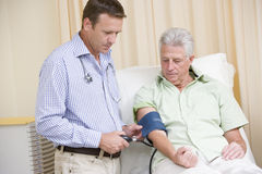 Doctor que controla la presión arterial del hombre Fotografía de archivo libre de regalías