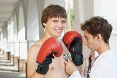 Doctor que controla a un boxeador sonriente Imagen de archivo