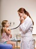 Doctor que da chequeo de la muchacha en oficina del doctor Fotografía de archivo