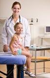 Doctor que da chequeo de la muchacha en oficina del doctor Imagen de archivo