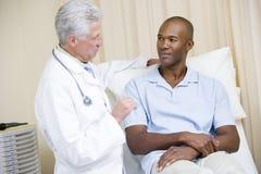 Doctor que da chequeo del hombre en sitio del examen Imagenes de archivo