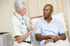 Doctor que da chequeo del hombre en sitio del examen Imagen de archivo libre de regalías