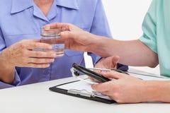Doctor que da el vidrio de agua Imagen de archivo