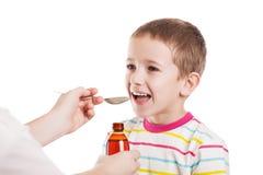 Doctor que da la cuchara del jarabe al muchacho Imágenes de archivo libres de regalías