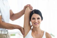 Doctor que da la fisioterapia a la mujer embarazada fotografía de archivo libre de regalías