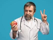 Doctor que da la manzana para la consumición sana Imagen de archivo libre de regalías