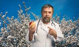 Doctor que da la manzana para la consumición sana Fotografía de archivo libre de regalías