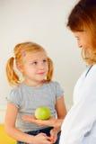 Doctor que da la manzana verde a la muchacha Fotografía de archivo libre de regalías