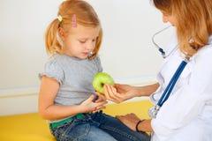 Doctor que da la manzana verde a la muchacha Imagenes de archivo