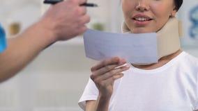 Doctor que da la prescripción a la mujer sonriente en cuello cervical de la espuma, seguro metrajes