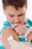 Doctor que da una inyección del niño en brazo Imágenes de archivo libres de regalías